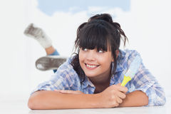 Smiling woman lying on floor holding paint brush Stock Image