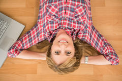Smiling woman lying on floor next to laptop Stock Images