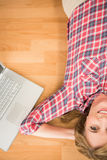 Smiling woman lying on floor next to laptop Royalty Free Stock Image