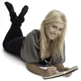 Smiling woman lying on floor with notebook. Happy young woman lying on studio floor writing in notebook stock image