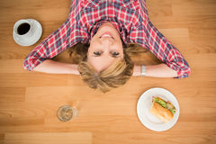 Smiling woman lying on floor surrounded by food and drink Royalty Free Stock Images