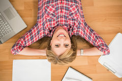 Smiling woman lying on floor surrounded by office items Royalty Free Stock Images