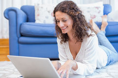 Smiling woman lying on the floor and using her laptop Royalty Free Stock Photography