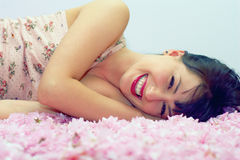 Smiling woman lying in flower petals. Beautiful smiling woman lying in flower petals Stock Photography