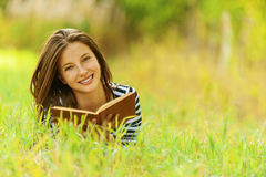 Smiling woman lying on grass Stock Photo