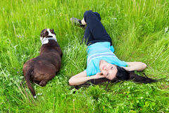 Smiling woman lying on the grass with dog Royalty Free Stock Image