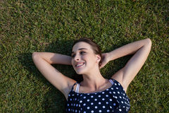 Smiling woman lying on grass with hands behind head Royalty Free Stock Photo
