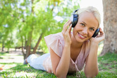 Smiling woman lying on the grass while listening to music Stock Photography