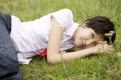 Smiling woman lying on grass in park Royalty Free Stock Photo