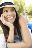 Smiling Woman Lying On Grass Wearing Sun Hat Stock Photo