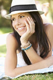 Smiling Woman Lying On Grass Wearing Sun Hat Stock Photography