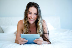 smiling woman lying on her bed on her tabet Stock Photos