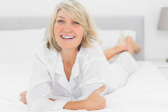 Smiling woman lying on her bed Stock Photography