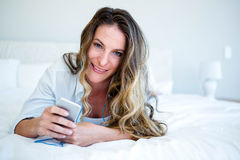 smiling woman lying on her bed listening to music Stock Photography