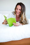 smiling woman lying on her bed reading a book Royalty Free Stock Photography