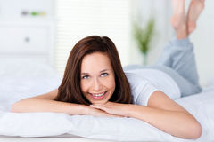 Smiling woman lying on her bed Stock Photo
