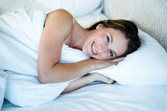 smiling woman lying in herr bed Royalty Free Stock Images