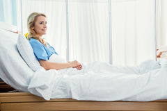Smiling woman lying in hospital bed Stock Images
