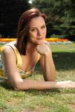 Smiling woman lying on lawn in sunny rose garden Royalty Free Stock Image