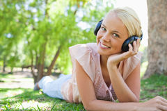 Smiling woman lying on the lawn while wearing headphones Royalty Free Stock Photography