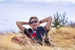 Smiling woman lying on a meadow  in a high mountain Stock Photo