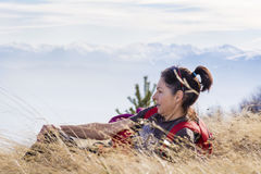 Smiling woman lying on a meadow  in a high mountain Stock Photography