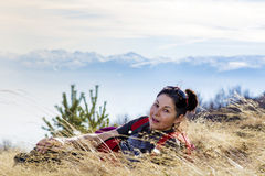 Smiling woman lying on a meadow  in a high mountain Stock Images