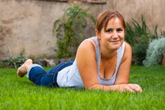 Smiling woman lying outdoors Stock Image