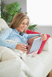 Smiling woman lying on a sofa drinking wine and using a tablet p Stock Image