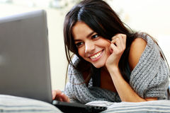 Smiling woman lying and typing on the laptop Royalty Free Stock Photos