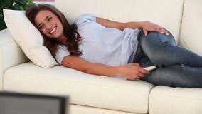 Smiling woman lying while watching the television stock video footage