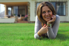 Smiling woman lying on the yard lawn. At home Stock Photos