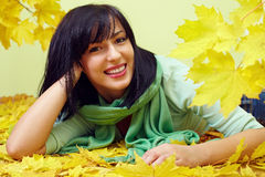 Smiling woman lying in yellow fallen leaves. Attractive smiling brunette woman lying in yellow fallen leaves, wearing green scarf Stock Photography