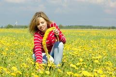 Smiling woman make dandelion wreath Stock Photos