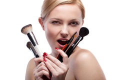 Smiling woman with make up brushes isolated Stock Images