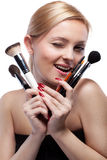 Smiling woman with make up brushes isolated Royalty Free Stock Image