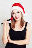Smiling Woman Makeup Artist in Christmas Santa Hat Royalty Free Stock Photography