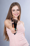 Smiling woman with makeup brushes Royalty Free Stock Photography
