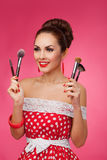 Smiling Woman with makeup brushes. She is standing Stock Image