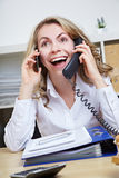 Smiling woman making calls with two Royalty Free Stock Photography