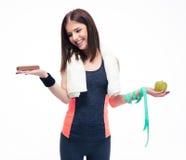 Smiling woman making choice between bananas and chocolate Stock Photos