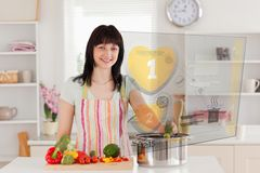 Smiling woman making dinner using hologram interface Stock Photography