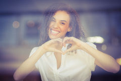 Smiling woman making heart shape Stock Photos