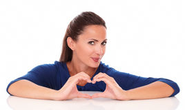 Smiling woman making a love sign Royalty Free Stock Photography