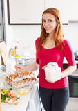 Smiling woman making omelet with flour Stock Photos