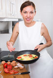 Smiling woman making omelet Stock Images
