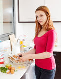 Smiling woman making  omelette Royalty Free Stock Photography