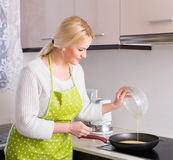 Smiling woman making omlet Stock Image