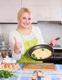 Smiling woman making  omlet Royalty Free Stock Photography