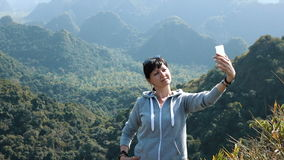 Smiling woman making selfie at the mountains background stock video